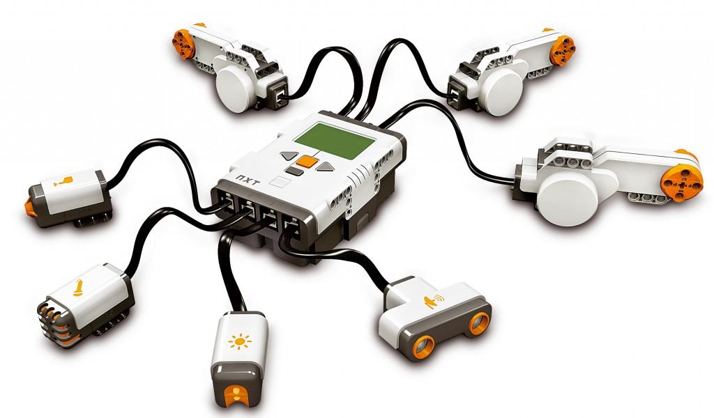 صورة توضيحية لأهم ميزات تقنية NXT. اللبنة NXT Brick في المنتصف، مع 3 محركات من نمط سيرفو، وحساس إضاءة وحساس صوت وحساس أمواج فوق صوتية وحساس لمس.